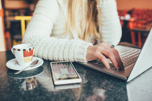 Close up on the hand of a young woman sitting on a bar having a coffee, using smart phone and tapping pc keyboard - leisure, technology, social network concept