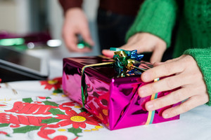 Close up on the hand of a young woman wrapping a christmas present, using scissor to make ribbon out of string - christmas, holiday