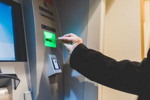 Close up on the hand of man inserting debit card in ATM machine - money, cash concept