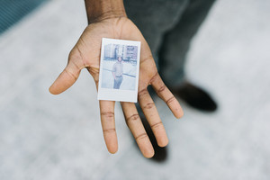 Close up on the hand of young handsome afro black man showing a photo of himself taken with instant camera - photography, creative, art concept