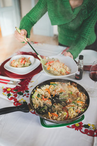 Close up on the hand of young handsome girl serving rice and vegetables from a pan to a plate using perforated spoon for chrismas meal - food, meal, veggie concept