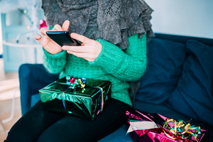 Close up on the hand of young handsome woman tapping on the screen of a smart phone sitting on the sofa with a wrapping gift leaning on her knee - technology, communication, social network concept