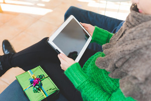 Close up on the hand of young handsome woman tapping on the screen of a tablet sitting on the sofa, gift place on her side- technology, communication, social network concept