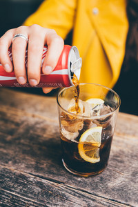 Close up on the hand of young woman porung soft drink into a glass with ice and lemon - drink, thirsty, refreshment concept