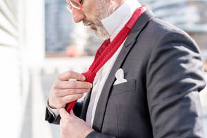 Close up on the hands of a man wearing neck tie - business, elegance concept