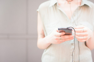 Close up on the hands of a woman holding a smartphone, listening music with headphones, tapping the screen - technology, music, communication concept