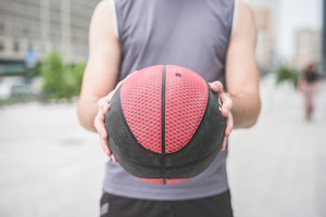 Close up on the hands of a young handsome caucasian sportive man holding a red and black basket ball - sportive, fitness, healthy concept