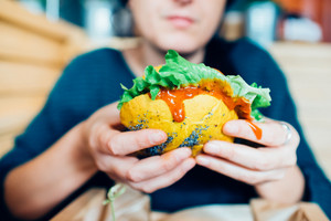 Close up on the hands of a young woman sitting holding a vegan burger - hunger, healthy, meal concept