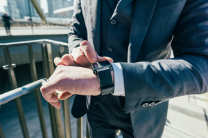 Close up on the hands of contemporary businessman using smart watch - technology, business, communication concept