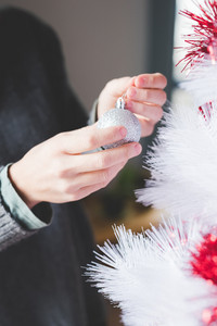 Close up on the hands of couple of young handsome caucasian woman decorating christmas tree - christmas, holiday, winter concept