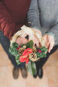 Close up on the hands of man and woman couple holding and showing a crown decoration - christmas, decoration, celebration concept
