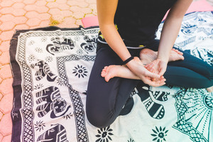 Close up on the hands of young woman doing yoga outdoor in lotus position - wellness, meditation, zen concept