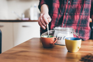Close up on the hands of young woman stir a cup of coffee at home - morning, refreshment, pause concept