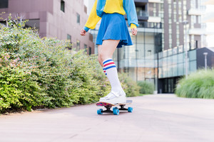 Close up on the legs of young eccentric woman skateboarding outdoor in the city - sportive, fashionable concept