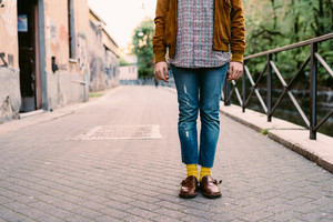 Close up on the legs of young man wearing jeans and denim, with yellow socks - style, fashion concept