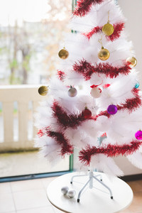 Close up on white chrismas tree decorated with colorful little ball and red decoration - christmas, celebration, adornments concept