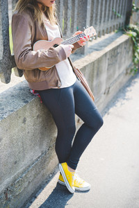 Close up on young woman playing ukulele - musician, composer, artist concept