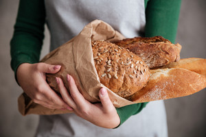 Close up photo of a female baker holding bag with bread in bakery