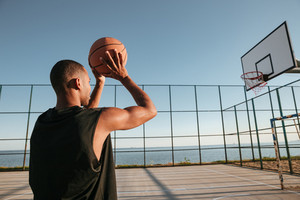 Close up portrait of a african basketball player throwing ball