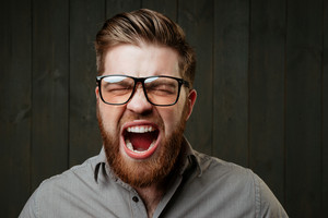 Close up portrait of a bearded casual man in eyeglasses screaming with eyes closed isolated on the black wooden background