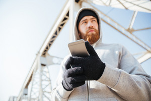 Close up portrait of a bearded young man in hoodie standing at the urban bridge with mobile phone