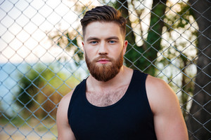 Close up portrait of a bearded young man standing and looking at camera outdoors