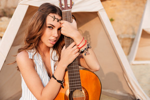 Close up portrait of a beautiful brunette hippie girl with guitar outdoors at the beach