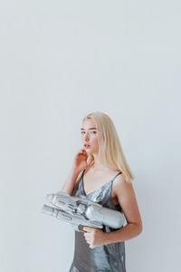 Close up portrait of a beautiful fashion blonde girl in silver shiny dress holding water gun and posing isolated on the grey background