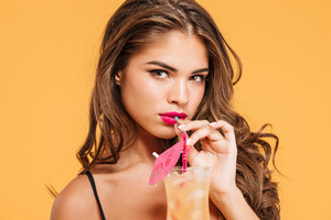 Close up portrait of a beautiful young sexy girl in bikini drinking cocktail isolated on the orange background