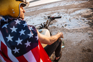 Close up portrait of a brutal man wearing golden helmet and american flag sitting on motorcycle