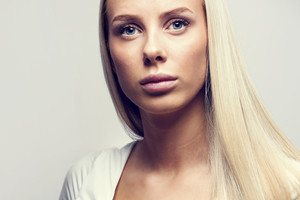 Close-up portrait of a casual blonde woman in white top