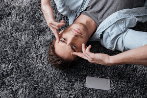 Close up portrait of a casual man lying on a carpet and intensely thinking