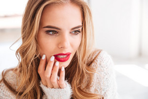 Close up portrait of a charming pretty woman with red lipstick indoors