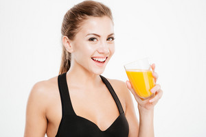 Close up portrait of a cheerful smiling woman with glass of orange juice isolated on a white background
