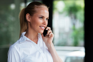 Close up portrait of a cheerful young businesswoman standing and talking on mobile phone outdoors