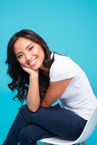 Close up portrait of a cheerful young vietnamese woman sitting on the chair isolated on a blue background