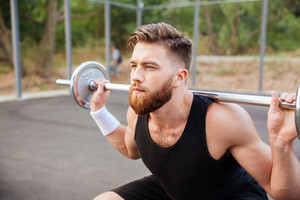 Close up portrait of a concentrated bearded sports man doing squatting exercises with barbell outdoors