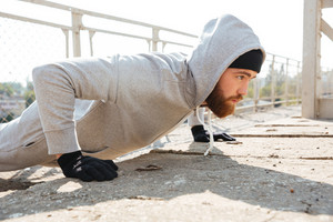 Close up portrait of a concentrated sports man doing push ups outdoors