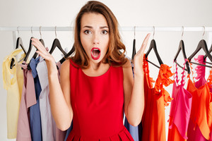 Close up portrait of a confused lovely woman in red dress choosing what to wear isolated on a white background