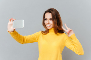 Close up portrait of a cute lovely playful young woman taking selfie with mobile phone over gray background