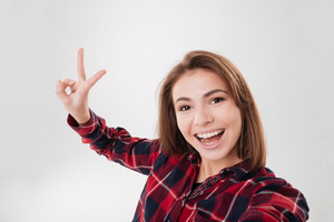 Close up portrait of a cute lovely woman taking selfie and showing peace sign with fingers over white background
