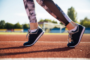 Close up portrait of a female runner feet running on stadium outdoors