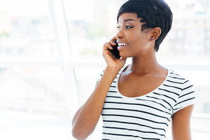 Close up portrait of a happy african american young businesswoman standing in office and talking on cell phone