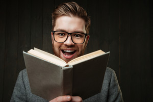 Close up portrait of a happy cheerful man in eyeglasses reading book isolated on the black wooden background