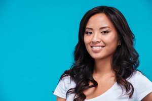 Close up portrait of a happy smiling asian woman isolated on blue background