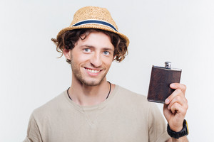 Close-up portrait of a happy young man holding alcohol flask isolated on the white background