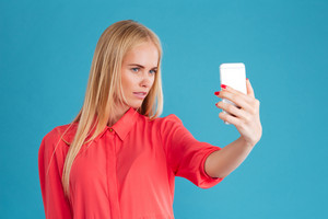 Close up portrait of a happy young woman making selfie photo on smartphone over blue background