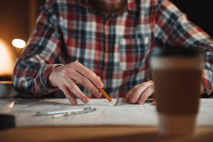 Close up portrait of a man hands drawing graph on a desk with cup of coffee