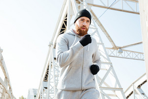 Close up portrait of a man jogger running across bridge in the morning
