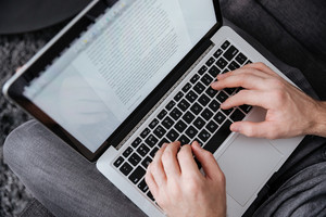 Close up portrait of a man typing on laptop while sitting on sofa